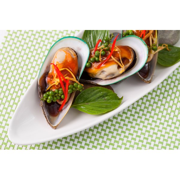 An appetizer of green-lipped mussels on a plate.