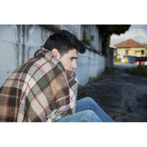 A young man sits on a street corner wrapped in a blanket.