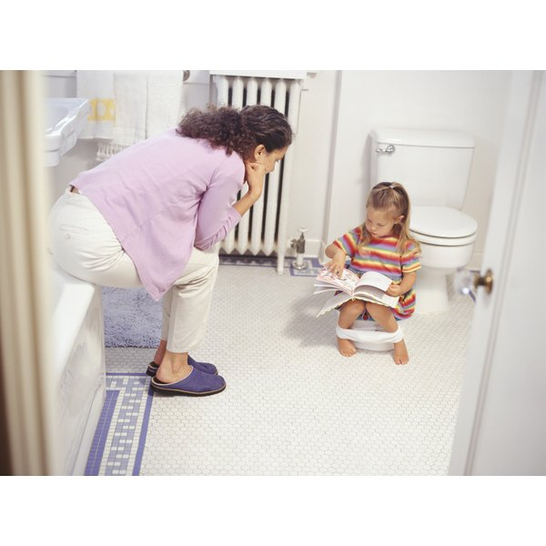 Mother teaching daughter to use a potty