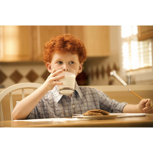 A boy drinks milk at the dinning table.