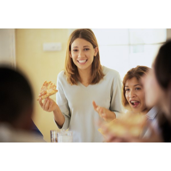 A woman holding a slice of pizza.