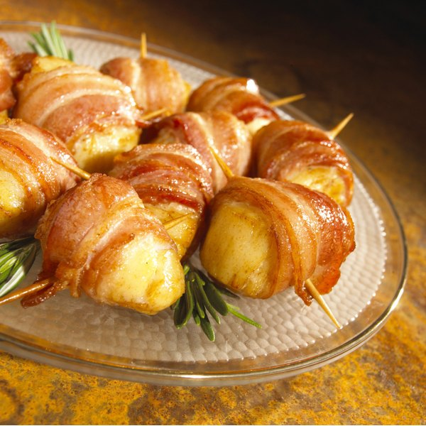 Bacon-wrapped scallops on a glass plate sit on a wooden table.