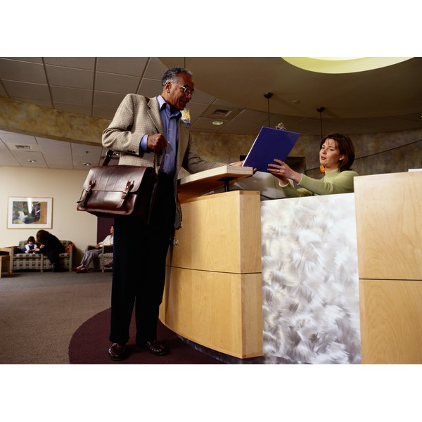 A man signs in at a hospital reception desk while the receptionist shows him a clipboard.