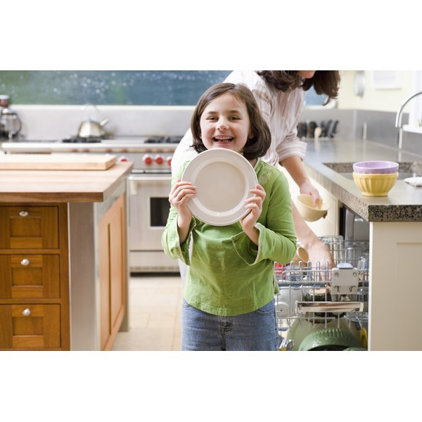 A girl helps her mother unload the dishwasher.