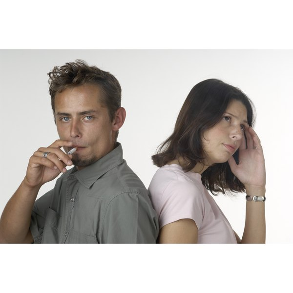 Young woman disapproving of male's smoking habit.