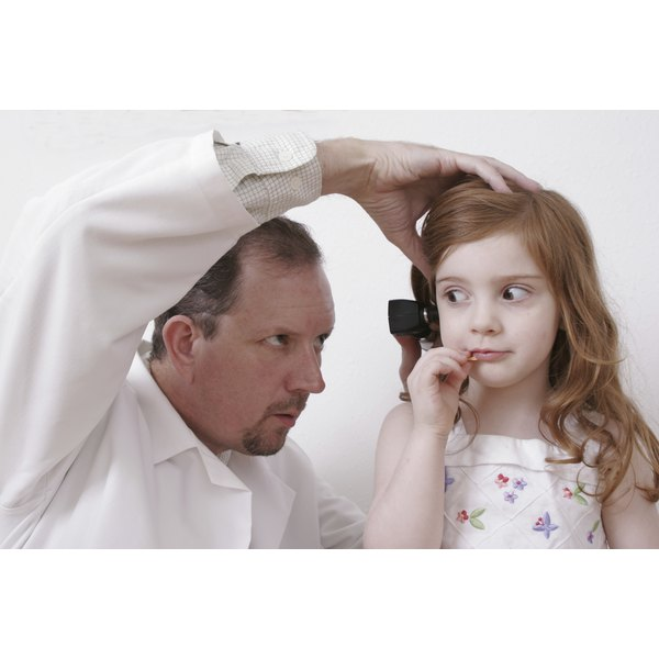 A doctor examining a child's ear.