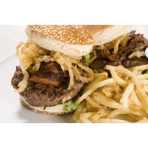 Close-up of two Kobe beef burgers on a plate with French fries.