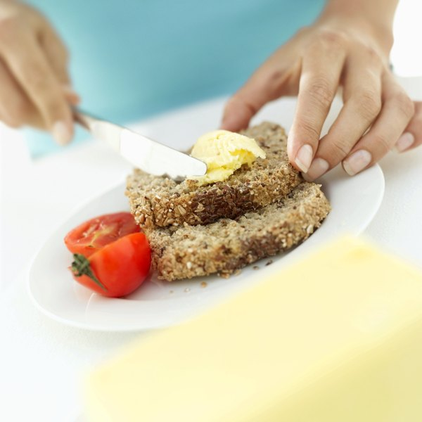 Close-up of a woman spreading butter on some bread.