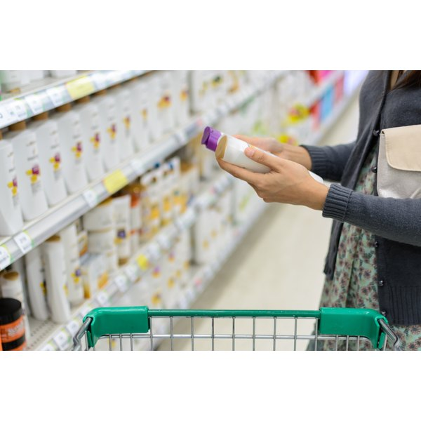 A woman is shopping for shampoo.