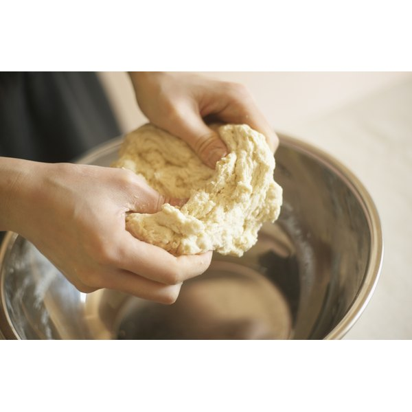A woman is kneading dough.