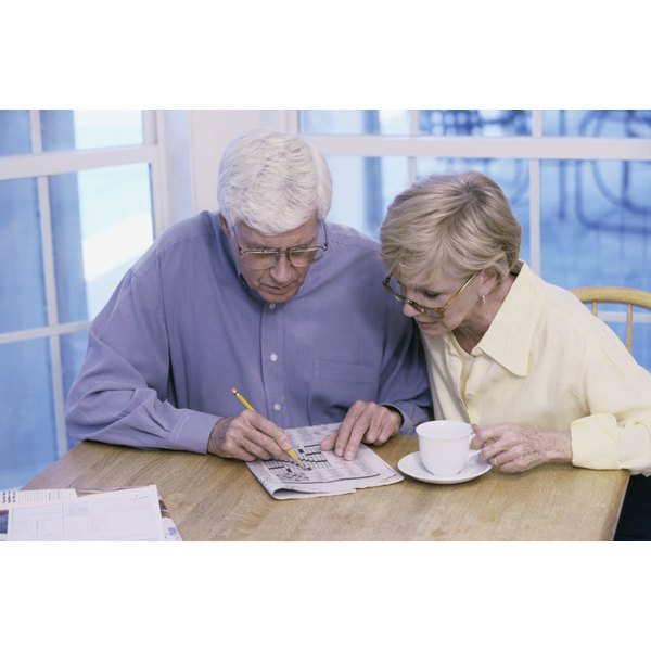Close-up of a senior couple doing the crossword puzzle together.