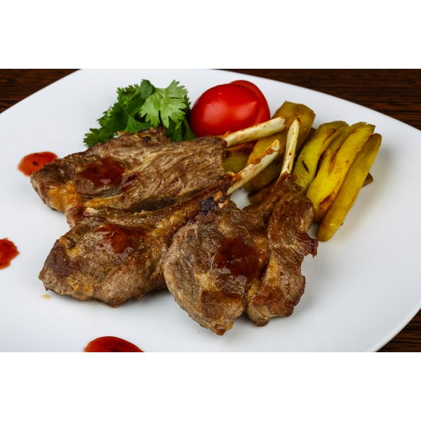 A plate of grilled lamb chops and vegetables.