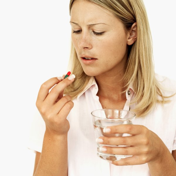 A woman is taking a supplement pill.