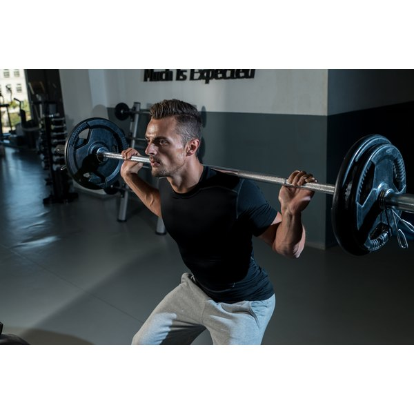A man is doing barbell squats.