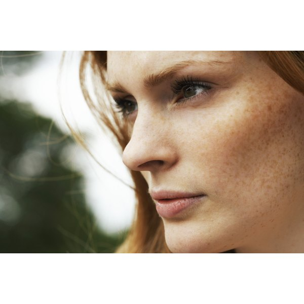 A close-up of a beautiful woman with freckles on her face.