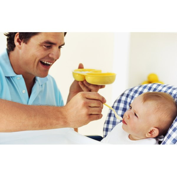 A father feeding his son in a highchair.