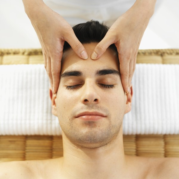 A man receives acupressure between the eyebrows.