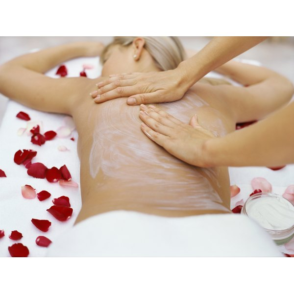 A woman has creme massaged into her back by a masseuse on a table with scattered rose petals.