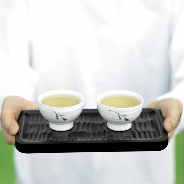 Two cups of green tea being served on a tray.
