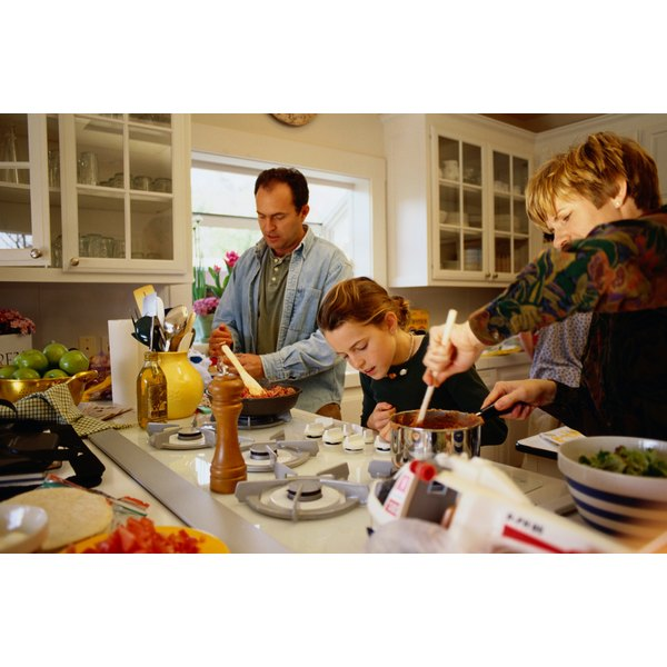 A family in the kitchen cooking.