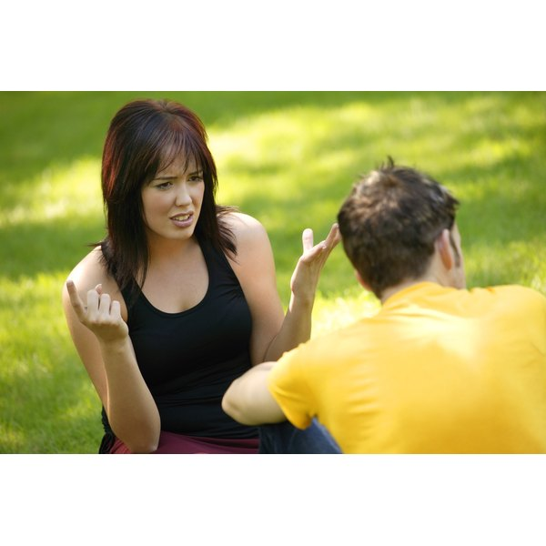 Young woman arguing with her boyfriend on the grass.