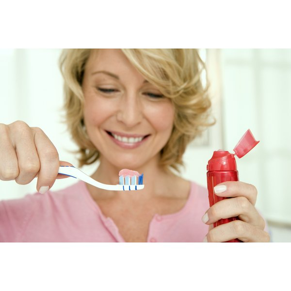 A woman putting toothpaste on her toothbrush.