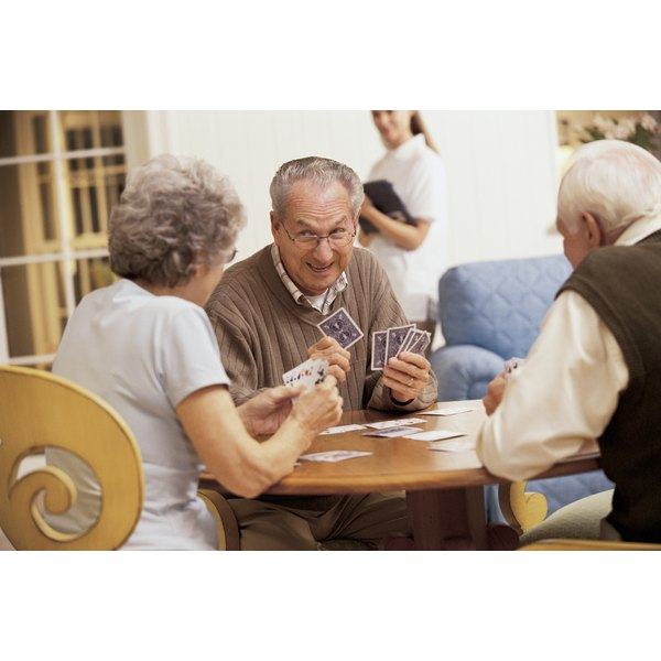 Three seniors play cards in a nursing home recreation hall.
