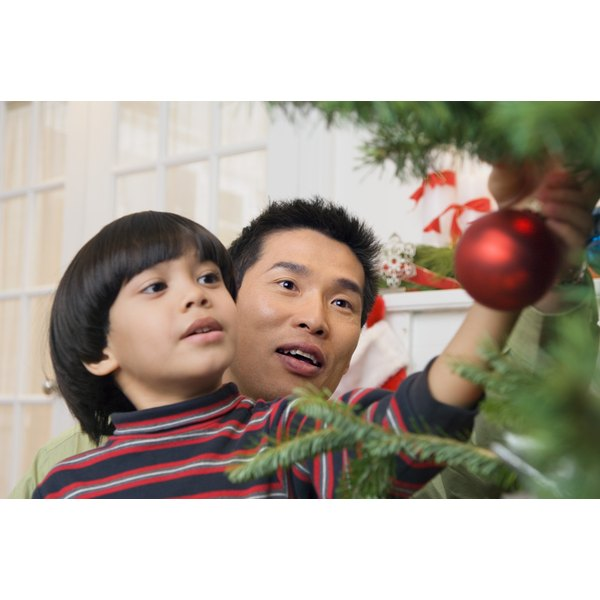 Father and son placing ornaments on christmas tree.