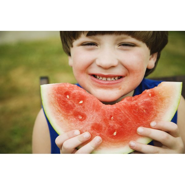 A boy is eating a slice of watermelon.