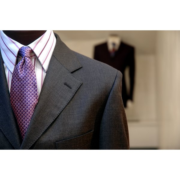 A close-up of two suits on display in a mens' clothing store.