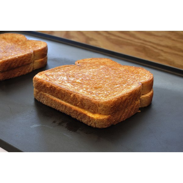 A grilled cheese cooking on a flat top griddle.
