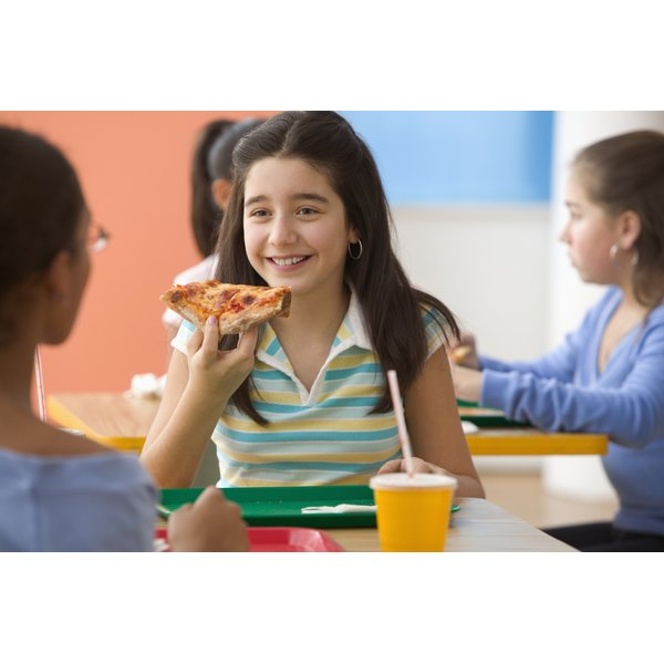 A girl eating a slice of pizza in a cafeteria with her friends.
