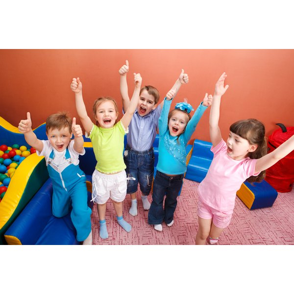 Preschoolers playing and jumping in a classroom.