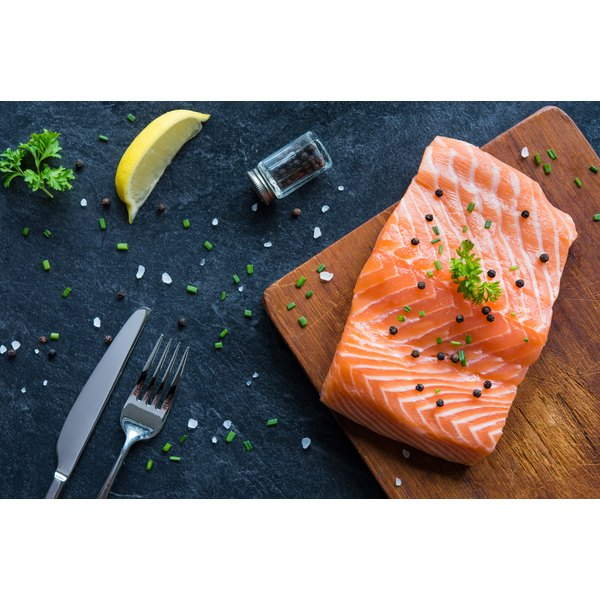 A piece of raw salmon on a cutting board.