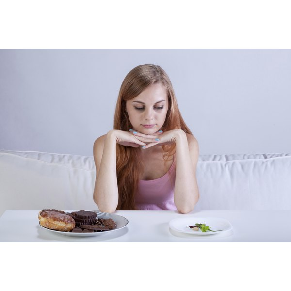 A skinny young girl is looking at two plates of food.