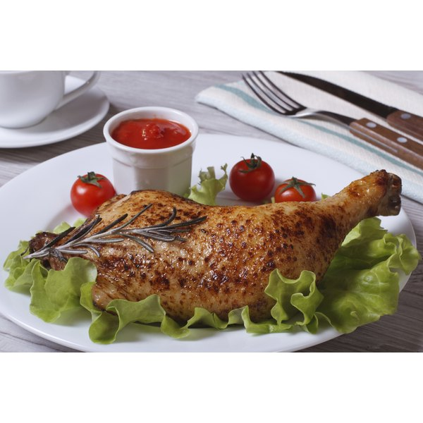 A grilled poultry leg on a plate.