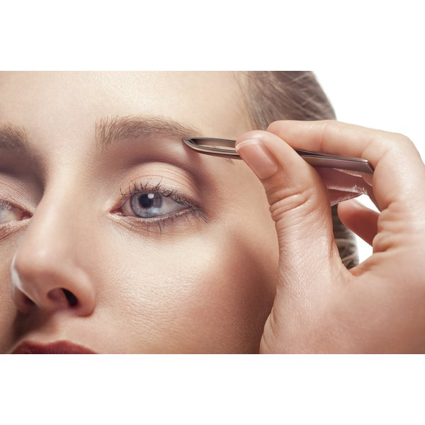 A close-up of a woman plucking her eyebrows.