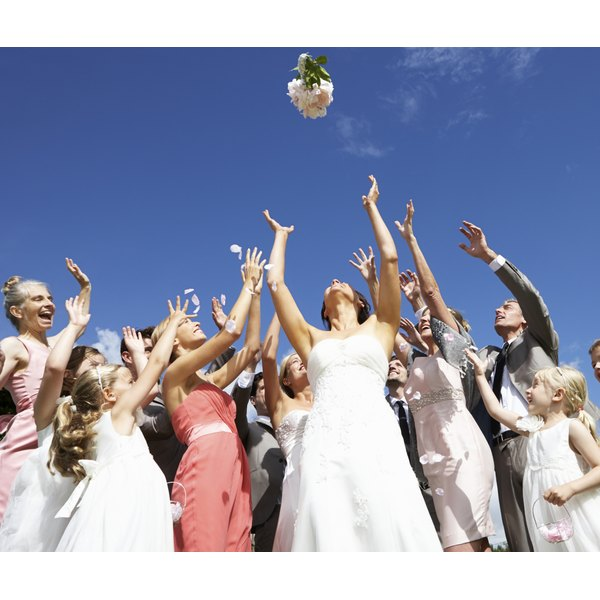 Quests try to catch a bridal bouquet at a wedding.