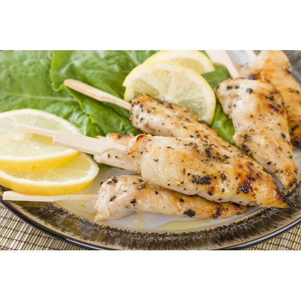 Grilled chicken sticks alongside some sliced lemon.