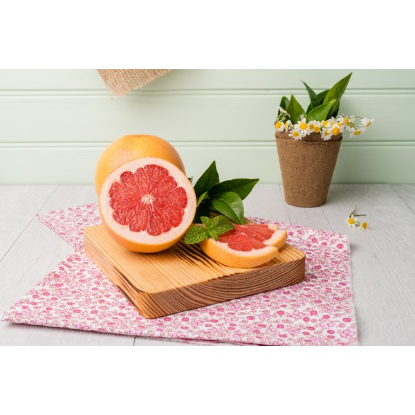Grapefruit slices on a wooden board.