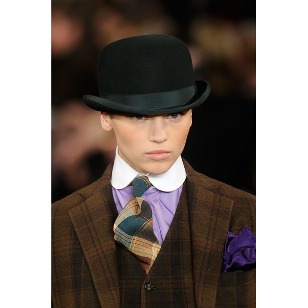 A runway model in a bowler hat and menswear inspired suit