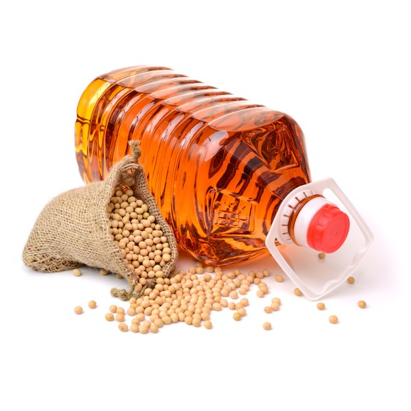 A bottle of soybean oil on a white counter with a small bag of soybeans spilling out of it.