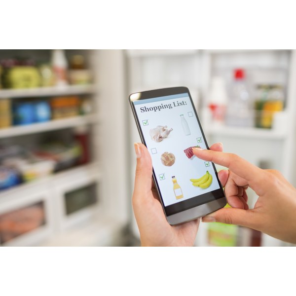 A woman is preparing a grocery list using her smartphone.