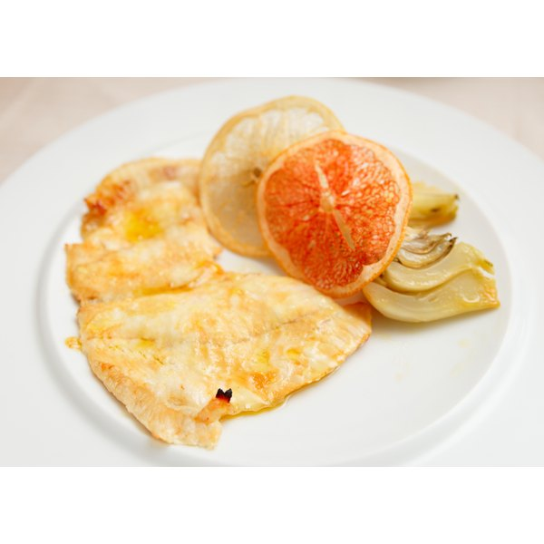 Branzino filets on a white plate with citrus garnish.