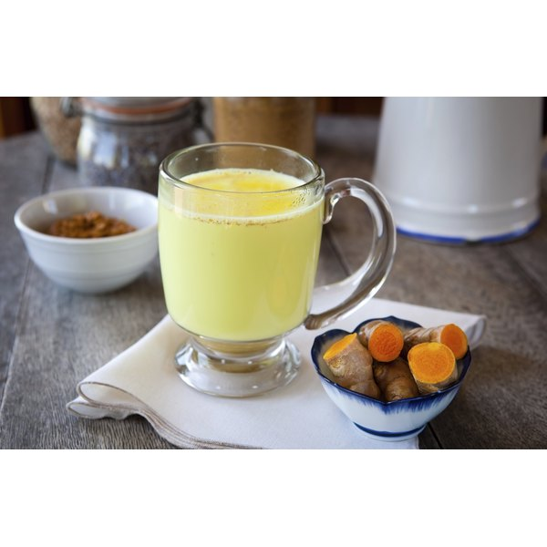 A hot drink made with turmeric, milk, honey, cinnamon and ginger next to a small bowl of fresh turmeric root.
