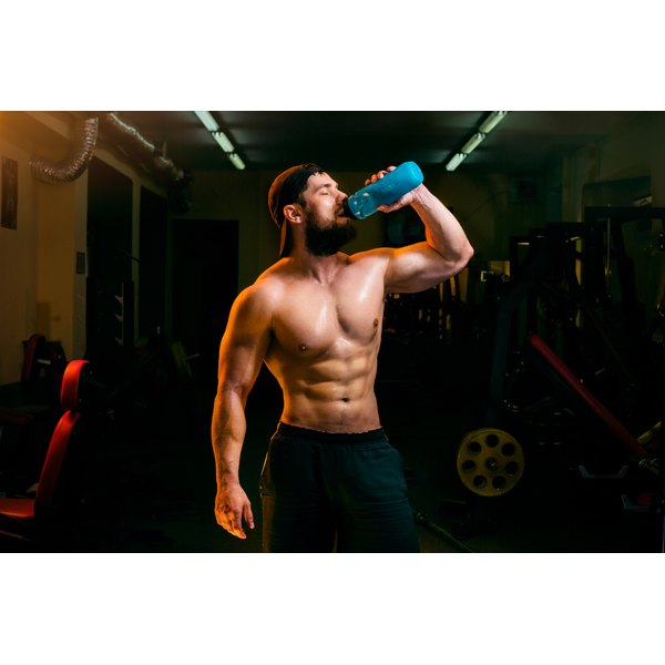 Bodybuilder chugs down a protein shake before a workout.