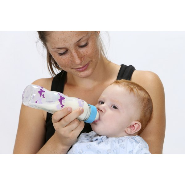 A woman is bottle feeding a baby.