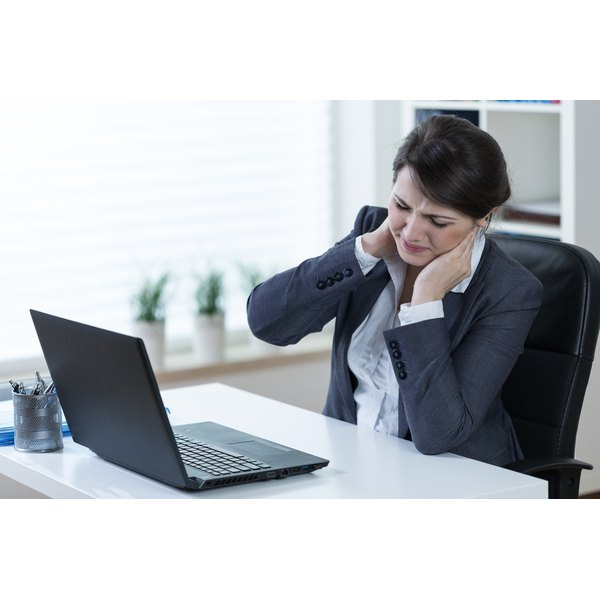 A young business woman sitting at her desk holding her neck in pain.
