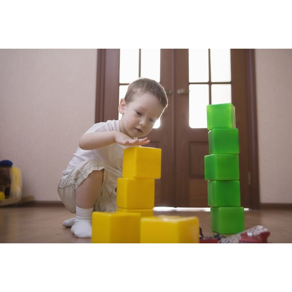 Child stacking yellow and green blocks.