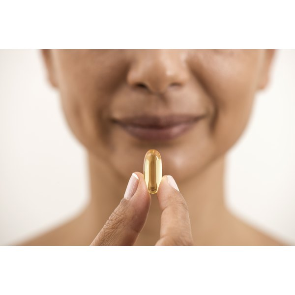 A woman is holding a fish oil pill in her hands.
